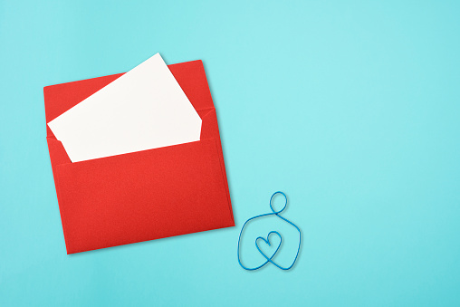 Red envelope with blank greeting card and blue wire heart shape