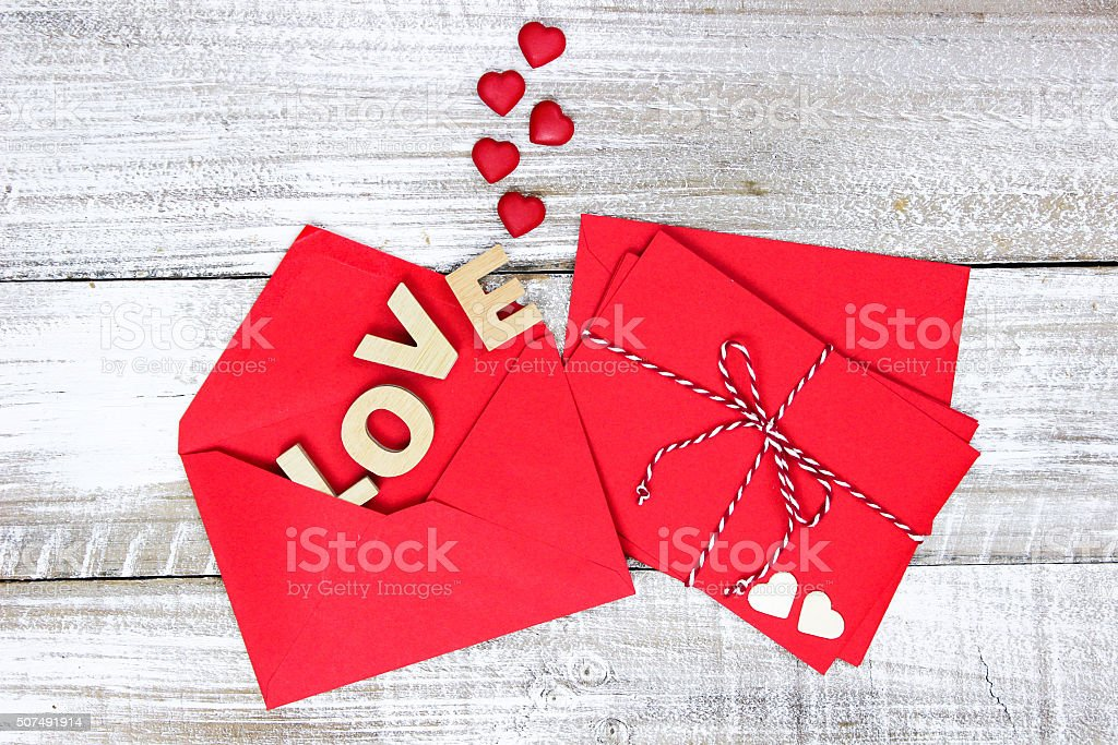 Red envelopes with hearts and LOVE on wood background stock photo