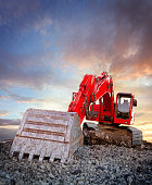 Red excavator at construction site