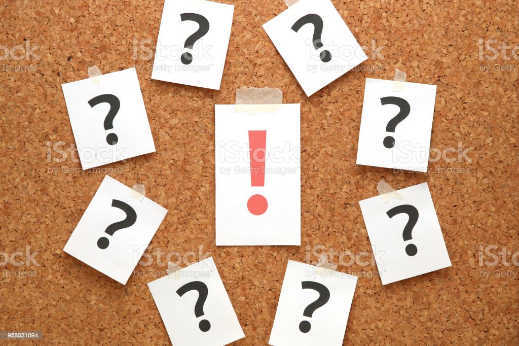 Red exclamation mark and many question marks on cork board. stock photo