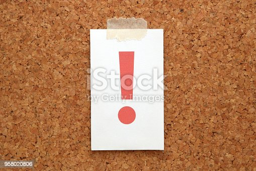 istock Red exclamation mark on a piece of paper on a cork board. 958020806