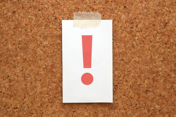 Red exclamation mark on a piece of paper on a cork board. stock photo