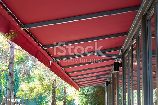 red fabric awning with steel structure roof of coffee shop in garden.