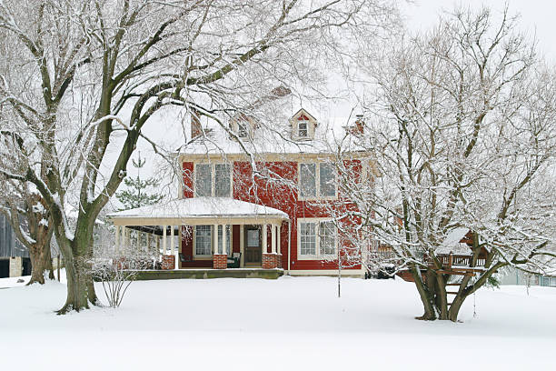 Red Farmhouse In The Winter Snow - Front stock photo