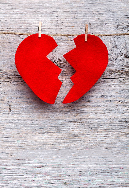 Red felt heart cracked in two on pegged to twine bildbanksfoto