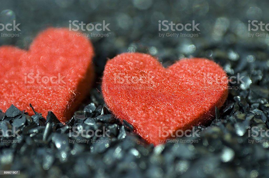 Red felt hearts on black gravel royalty-free stock photo