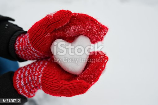 istock red female gloves hold a white heart from the snow 847125712