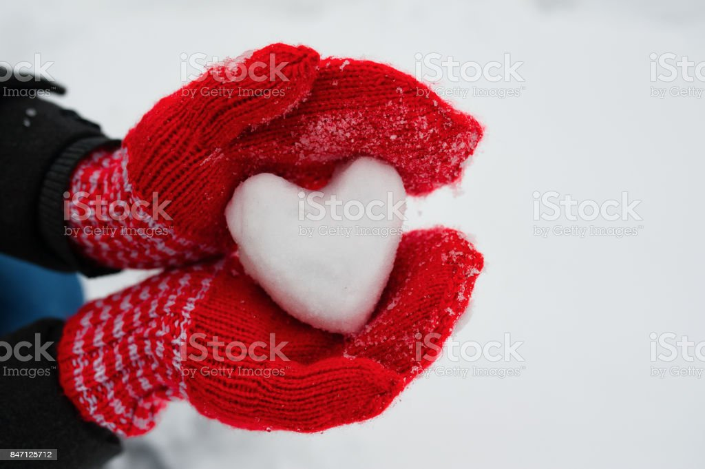 red female gloves hold a white heart from the snow stock photo