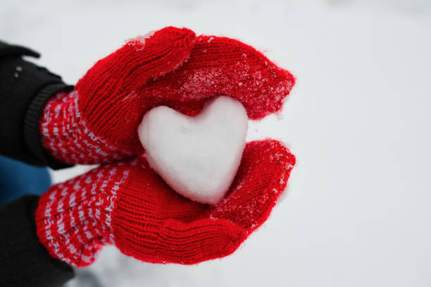 red female gloves hold a white heart from the snow - foto stock