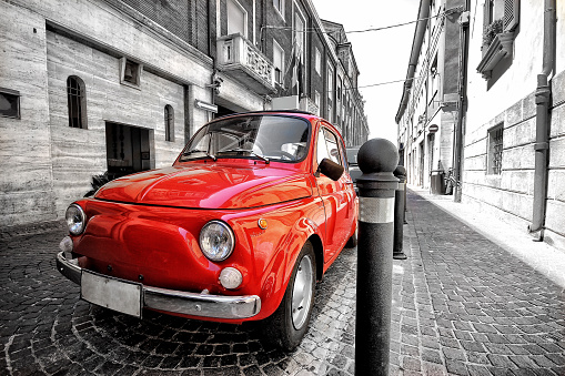 Red fiat 500 old vintage car in italy on a black and white background color splash postcard like photo