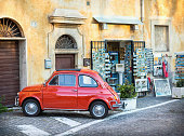istock Red Fiat 500 parked in front of a souvenir shop. 488210614