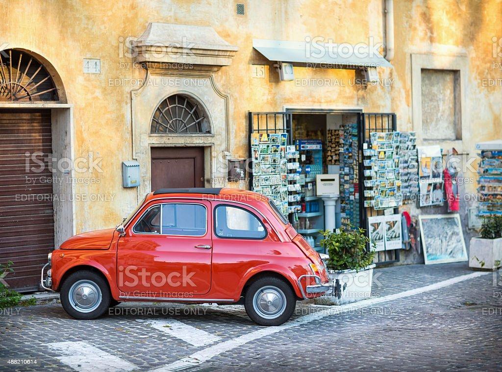 Rosso Fiat 500 parcheggiato davanti a un negozio di souvenir. - foto stock