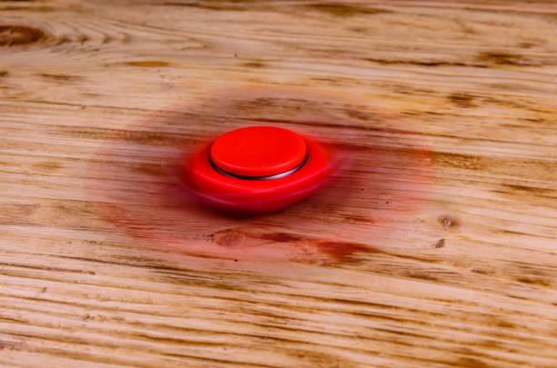 roten fidget spinner dreht sich auf schreibtisch aus holz - rot bekümmerte möbel stock-fotos und bilder