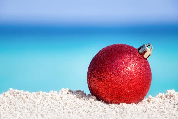 Red fir tree decoration ball on sandy beach stock photo