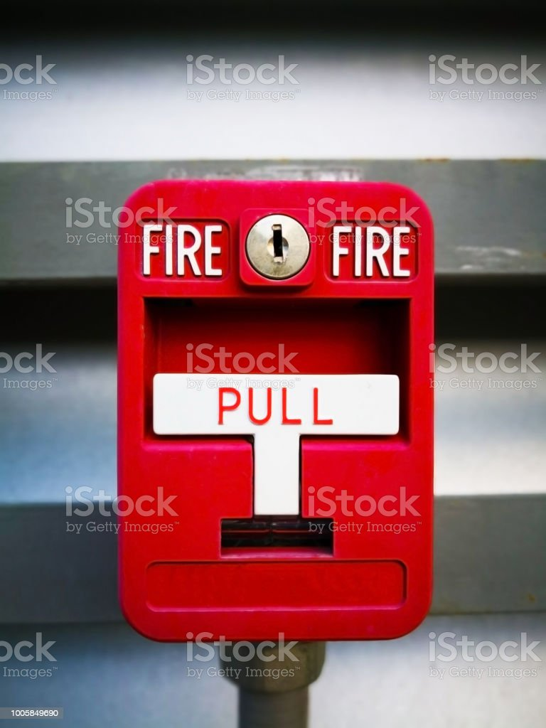 Red fire alarm box, is on grey metal wall for warning and security system. Pull danger fire safety box. Break red alarm equipment detector safe detector. stock photo