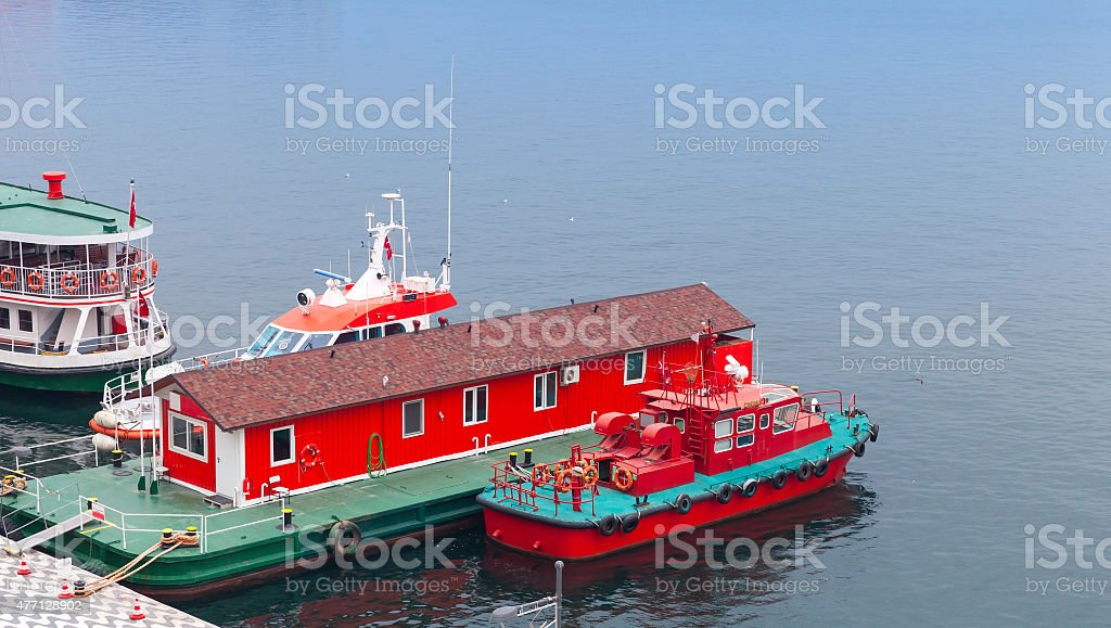 Red fire boat stand moored near floating fire station stock photo
