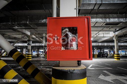 Red fire crane at underground parking with illuminated background