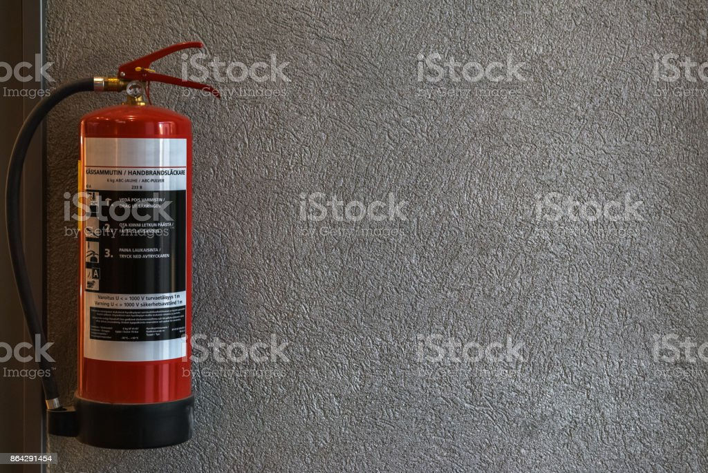 Red fire extinguisher hanging on the wall inside a shopping complex in the city of Lappeenranta, Finland. royalty-free stock photo