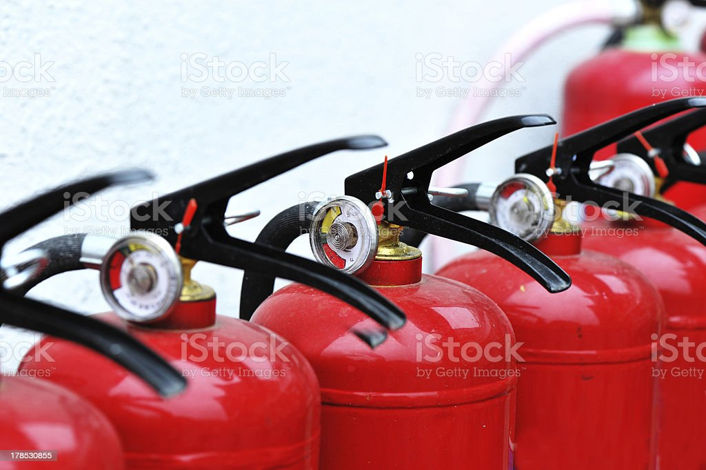 Red fire extinguishers lined up stock photo
