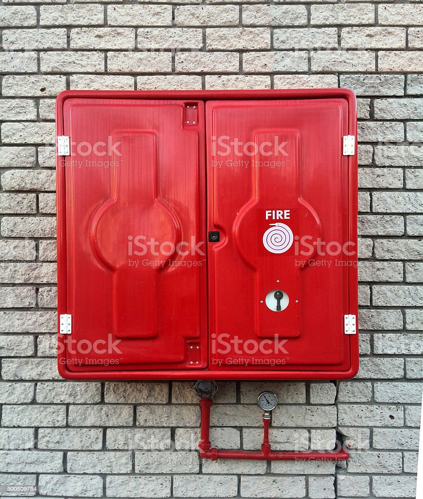 Red fire hose reel on crick wall stock photo