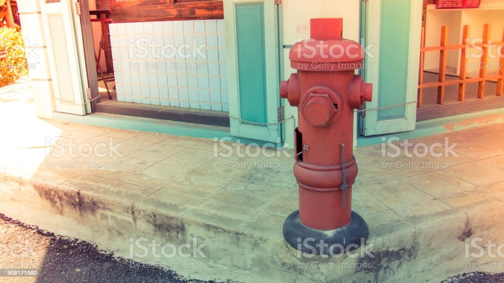 Old vintage red fire hydrant on street or footpath in front of store....