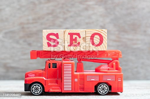 1045434476istockphoto Red fire truck hold letter block in word SEO (Abbreviation of search engine optimization) on wood background 1141709462