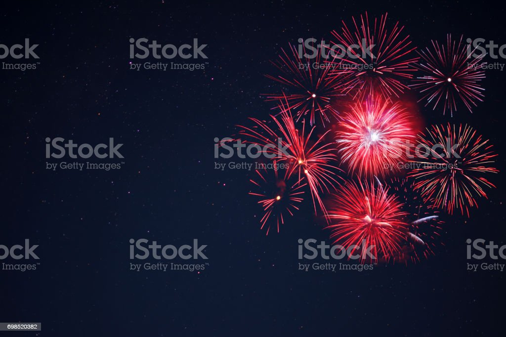 Red  fireworks located right side over night sky Amazing red celebration fireworks located right side over night sky, copy space.  Independence Day, 4th of July, New Year holidays salute background. Anniversary Stock Photo