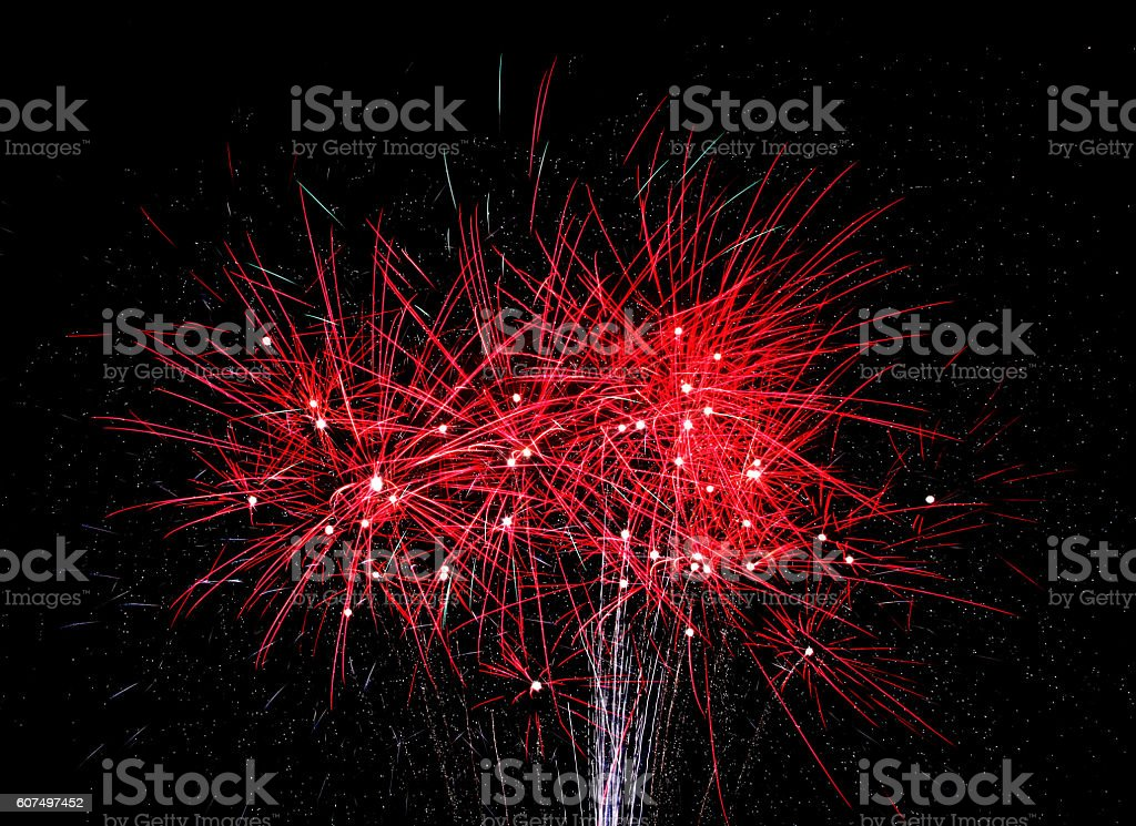 Red fireworks steam across the sky stock photo