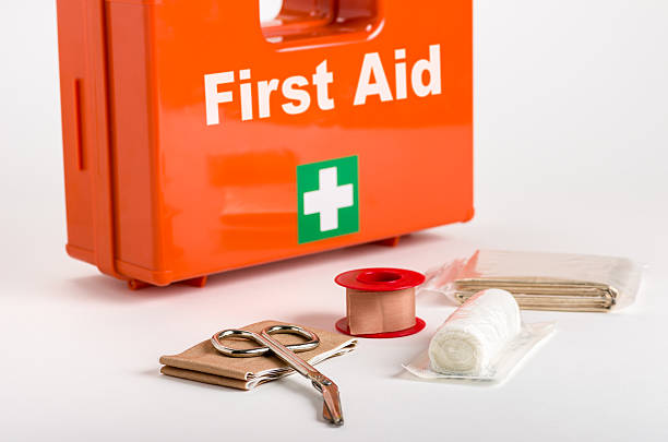 a red first aid box with supplies for dressings in front - first aid stock photos and pictures