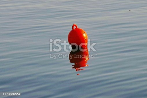 a picture of a small red fishhook in a sea,reflecting in the water,in small town in Greece,New Moudania