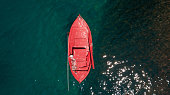 Aerial view of old red fishing boat anchored in the open sea