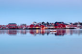 Red fishing warehouse with fishing boat reflection on coastline at evening