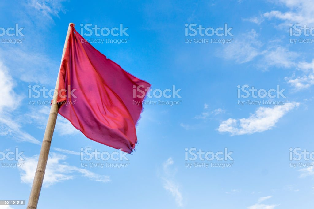 Red Flag against blue sky with clouds stock photo