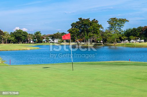 825397576 istock photo Red flag and sand bunker at the beautiful golf course at the lake side at sunset 855752846