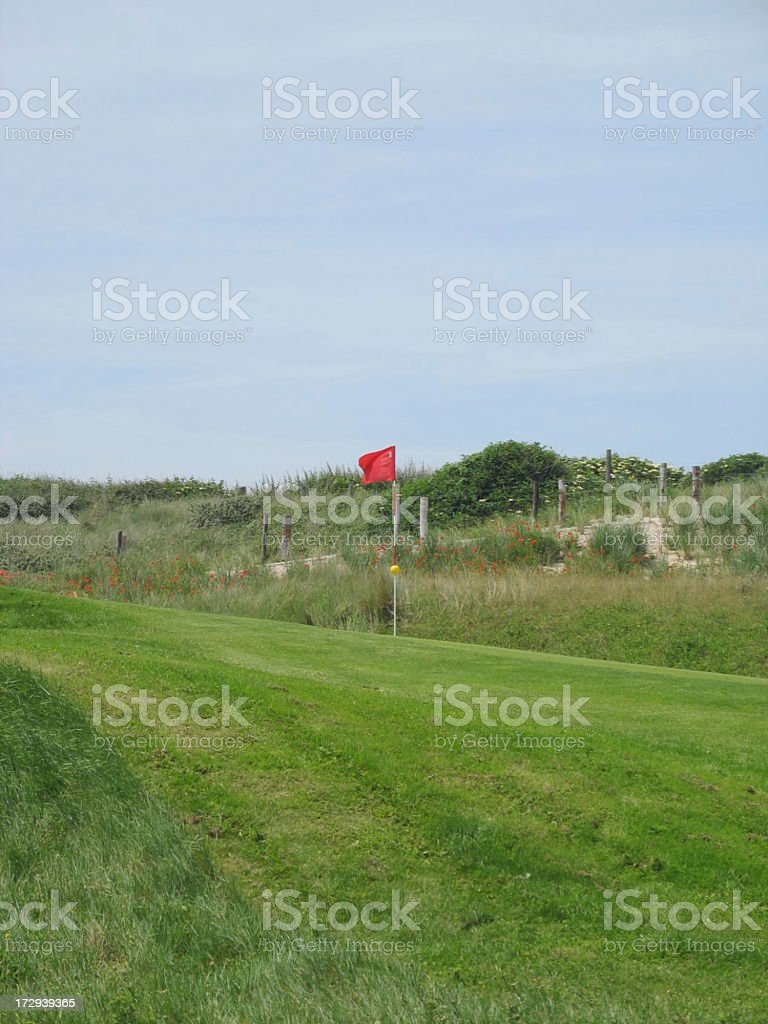 Red flag at hole on golf course royalty-free stock photo