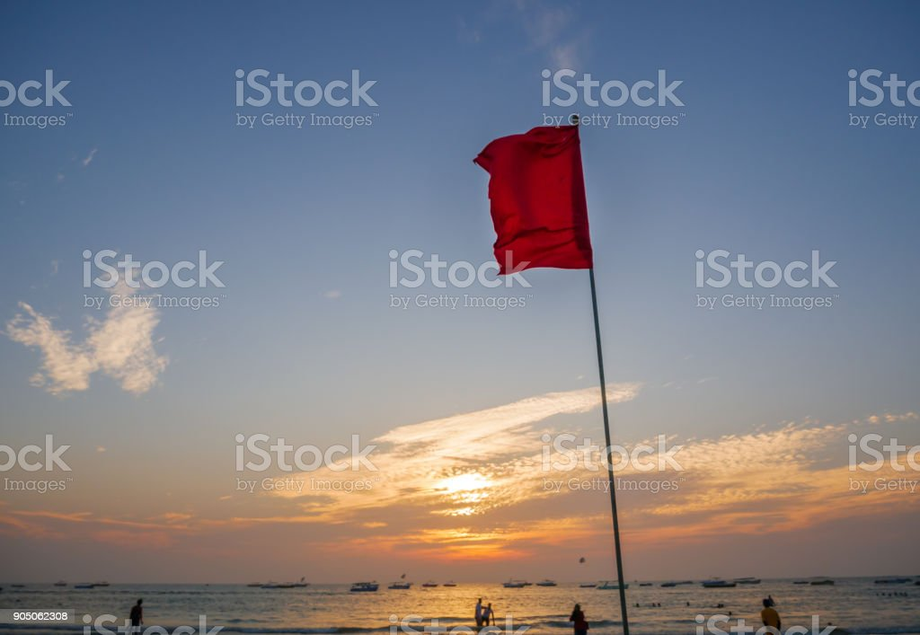 Red flag by the sea with sunset background stock photo