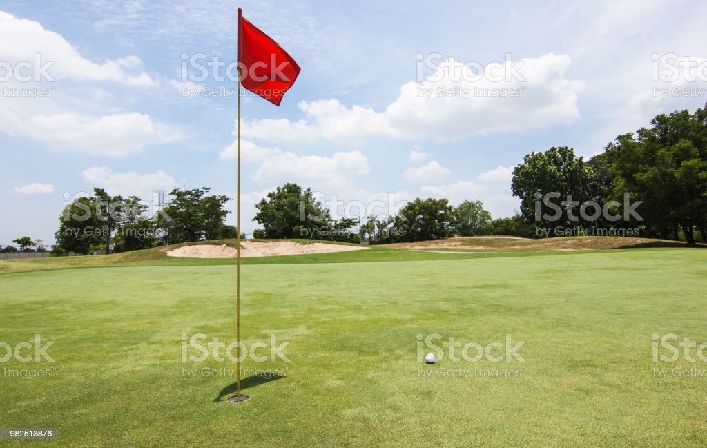 Red flag - Golf ball at the beautiful golf course of golf course...