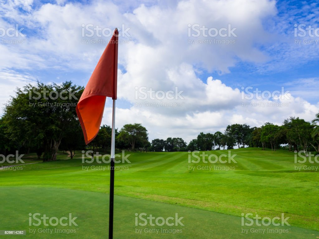 Red flag in a hole on a green at golf course with beautiful sunshine and blue sky scenic view in summer stock photo