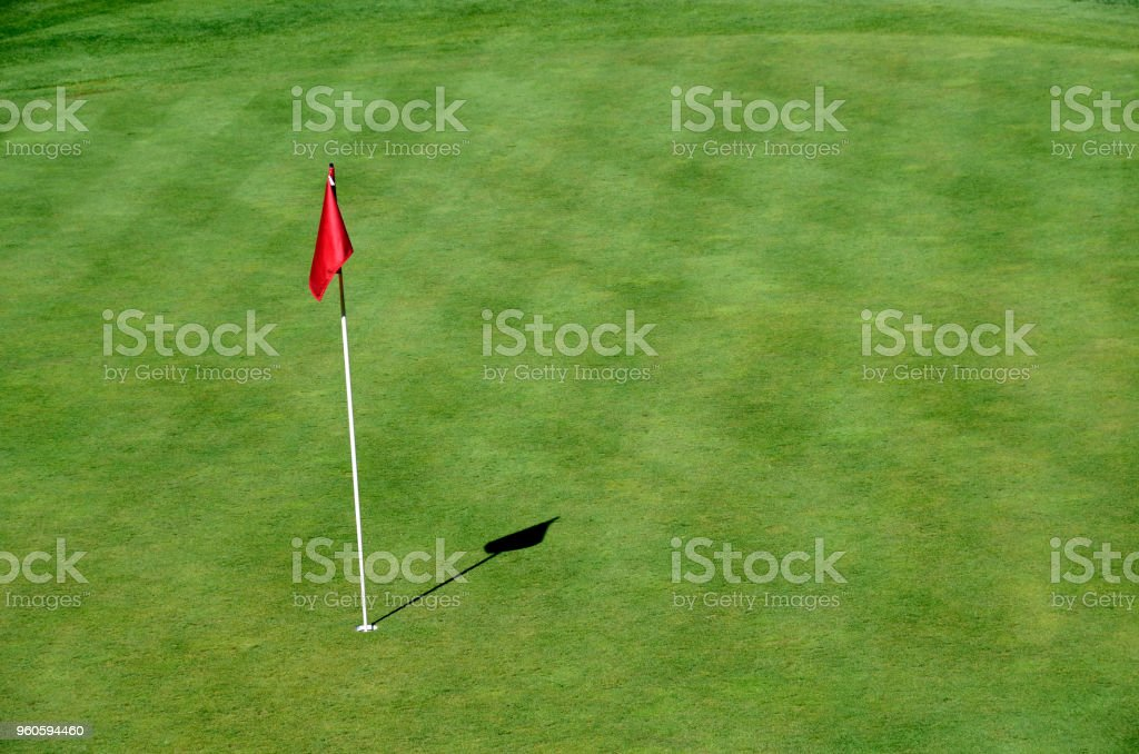 Red flag and green lawn on golf on Roc de cheres, in Talloires,...