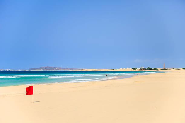 rote flagge am strand in kap verde boavista, - kapverdische inseln stock-fotos und bilder