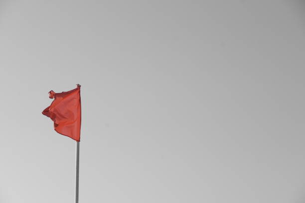 A red flag on the beach stock photo