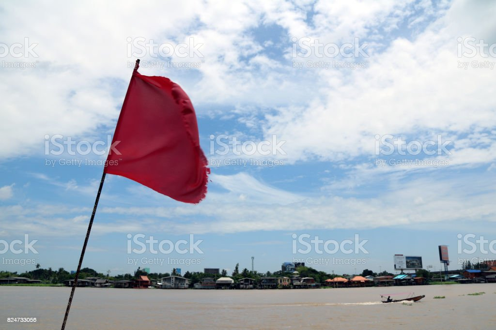 Red flag with blowing wind beside Chaophraya River. stock photo