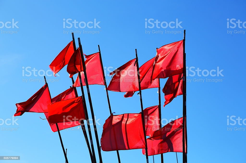 Red flags on blue sky stock photo