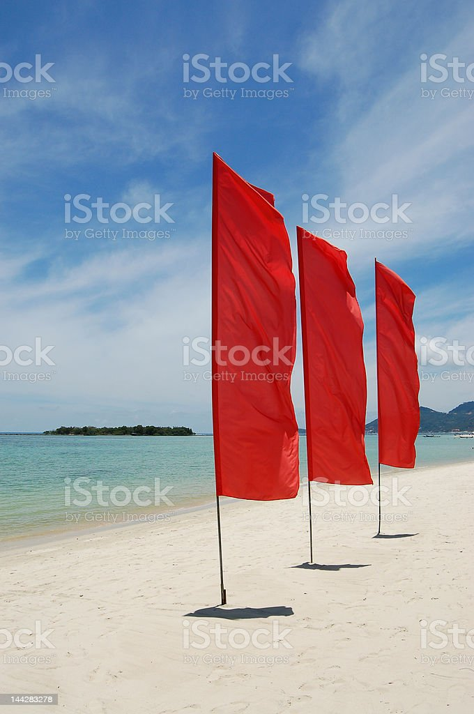 Red flags on white sand beach royalty-free stock photo