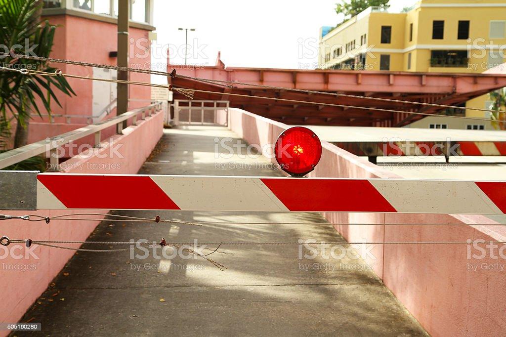Red flashing light and barricade on top of a drawbridge stock photo