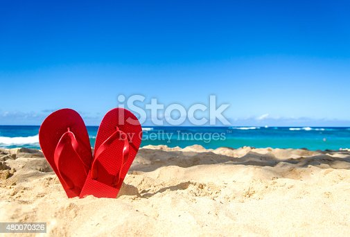 Red flip flops in heart shapes on the sandy beach in Hawaii, Kauai (romantic concept)