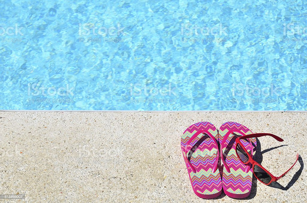 Red flip-flops and sunglasses beside blue pool stock photo