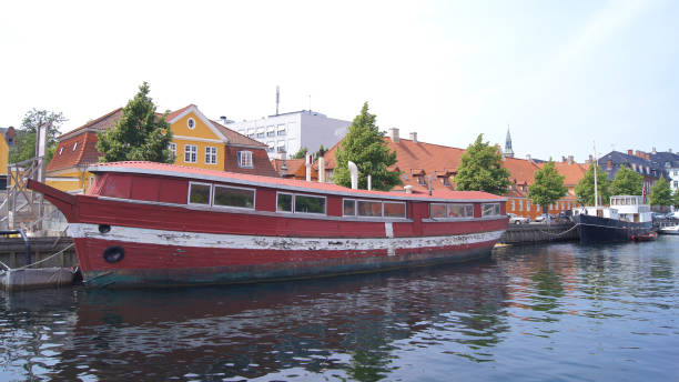 Red Floating house on city canal. Wodden House boat moored in a channel stock photo