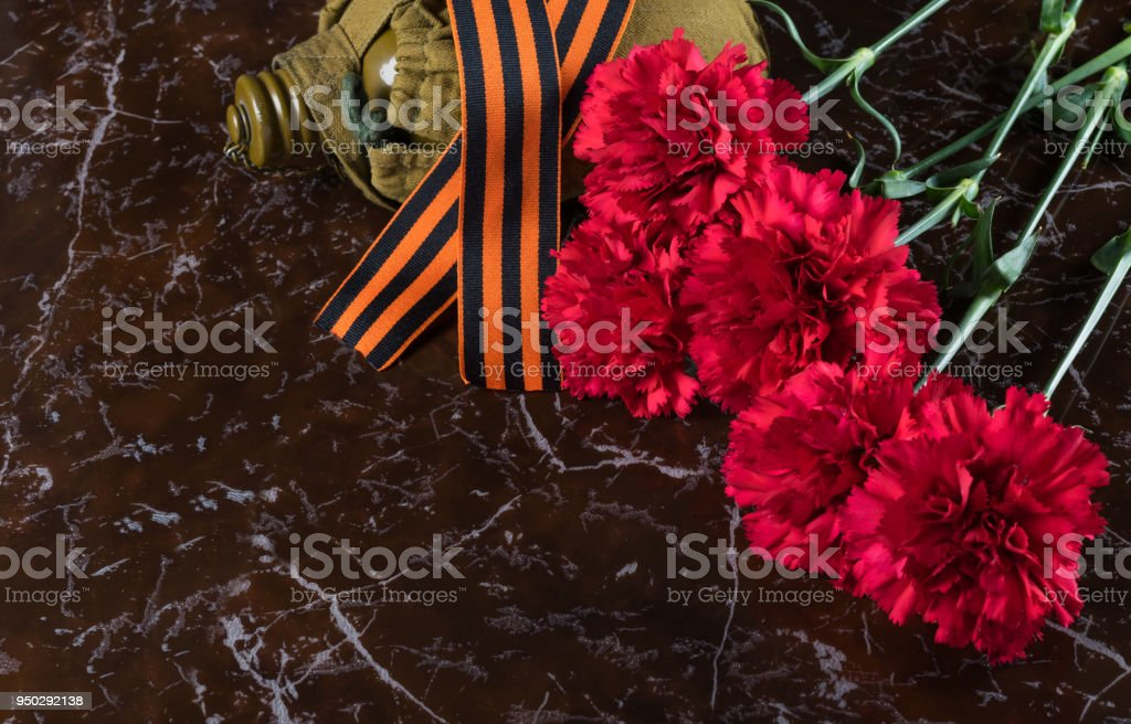 Red flowers and the St. George's ribbon lie on a marble slab stock photo