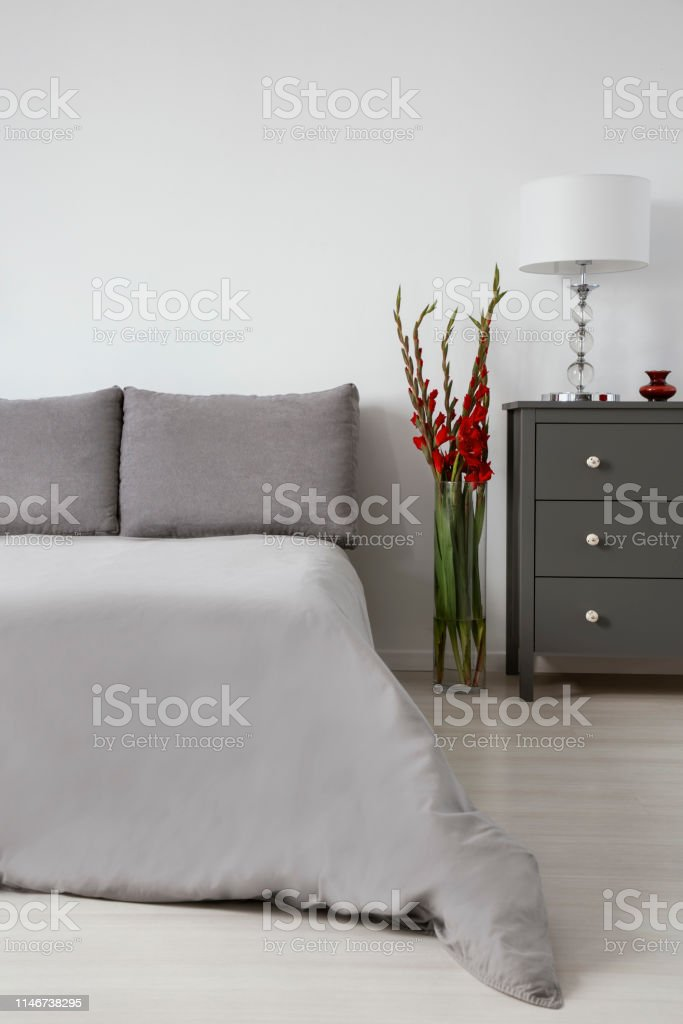 Red flowers in glass vase between king size bed with grey bedding and...
